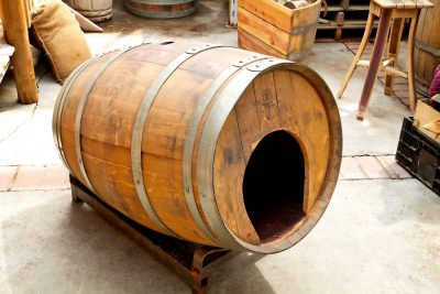 Rustic pet house made from a wine or whiskey barrel