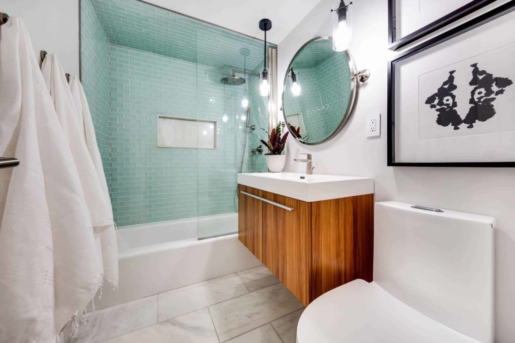 Modern green and white tile bathroom, wooden cabinet