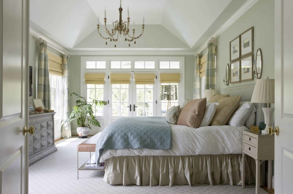 The subtle golden roman shades covering the French doors give an elegant twist to the more modern gray tones featured throughout the room.