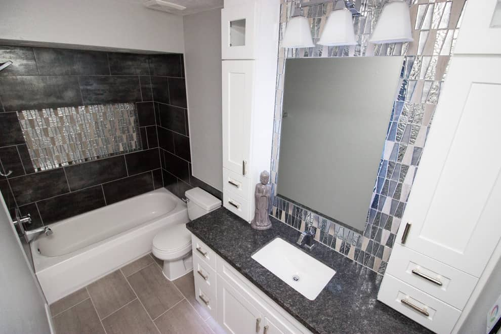 Grey tile floor, black tile walls, white cabinets, granite countertop