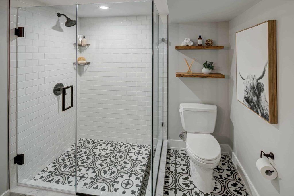 Small white tile corner shower, black and white floor pattern