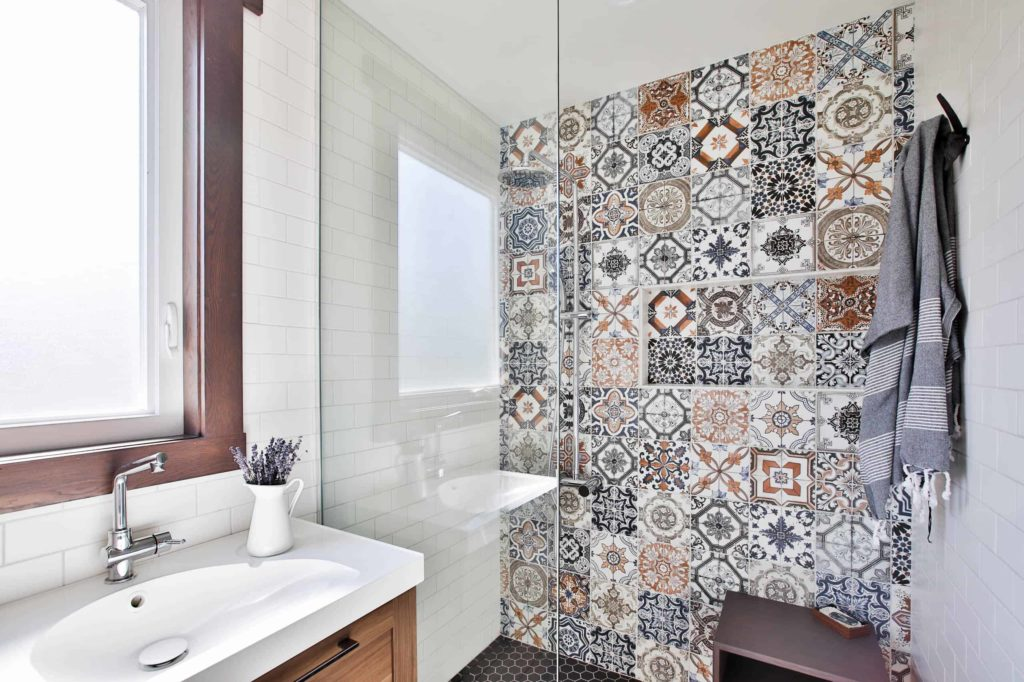Small white walk-in shower, multi-colored pattern wall