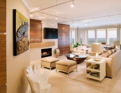 Spacious living room in beige colors in a house with tile floor, wooden panels on the walls, sofa, chairs and ottomans, a balcony with a view of the sea, a small fireplace and a TV above the fireplace