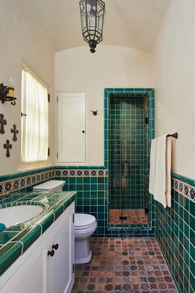 Alcove shower, green tile and beige walls, terracotta floor
