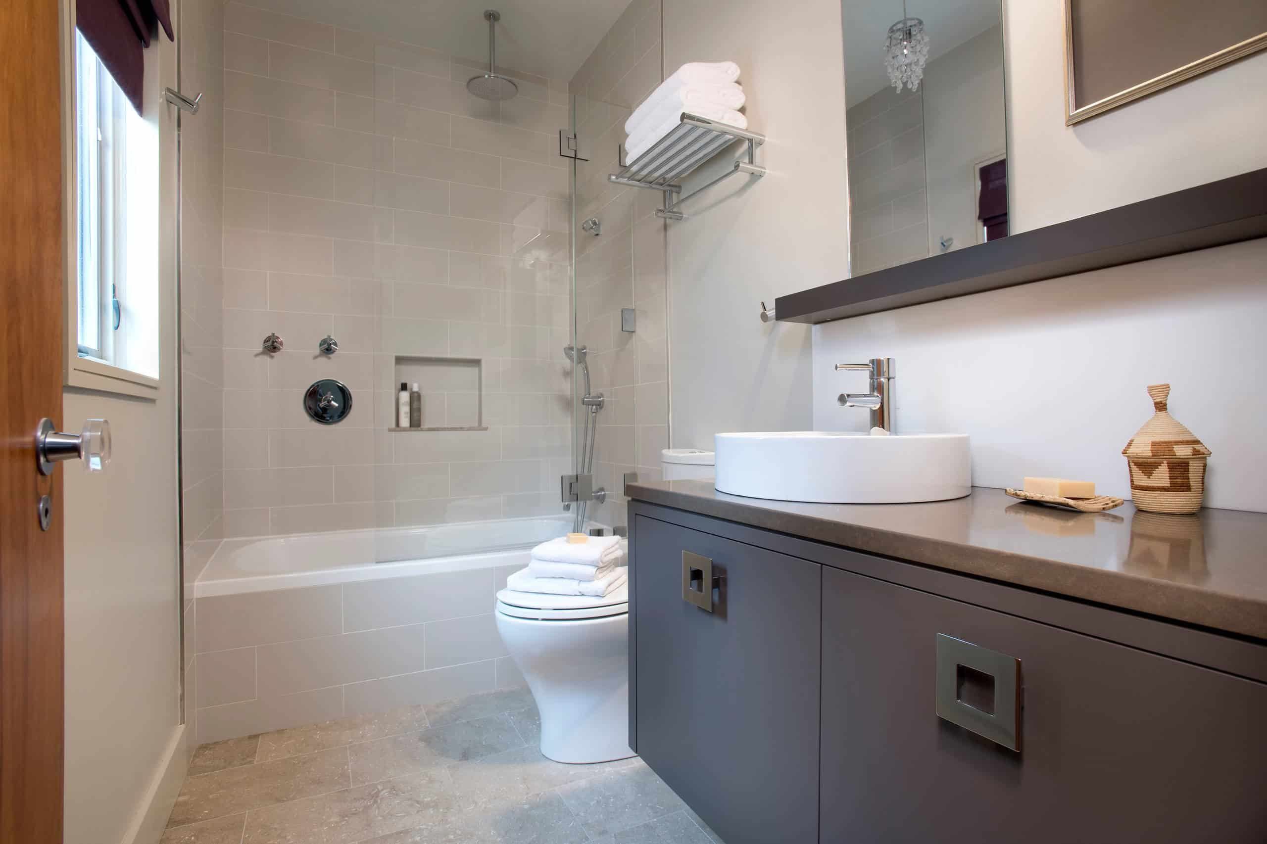 Minimalist bathroom, grey tile walls, grey limestone tile floor, brown cabinets