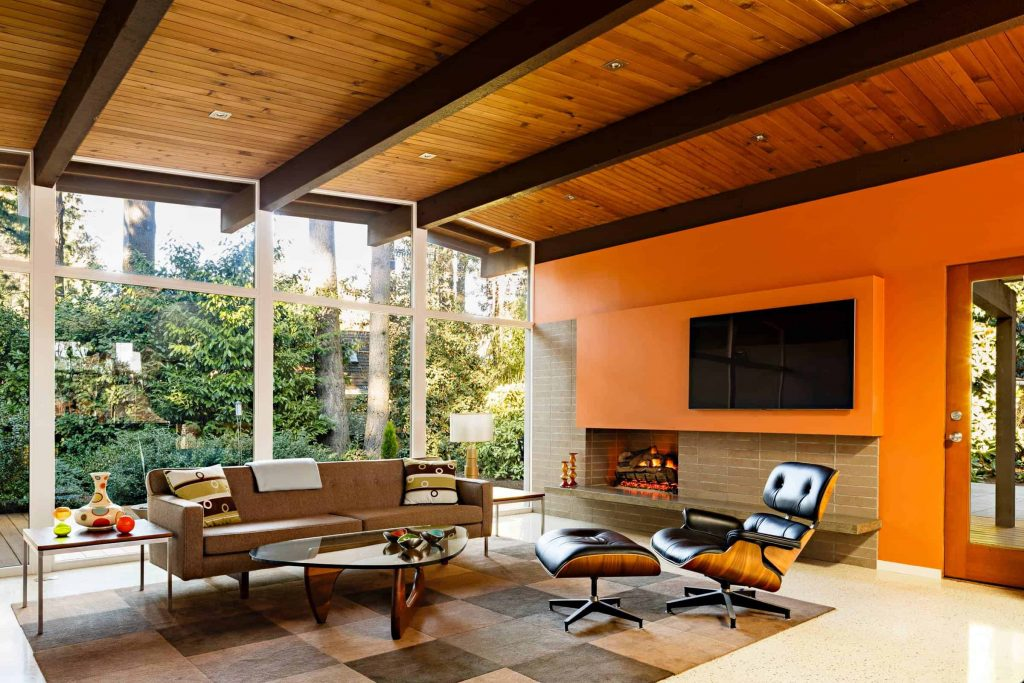 Spacious living room in a house with window wall, wooden ceiling, brown sofa and black armchair, brown brick fireplace and a TV above the fireplace on an orange wall