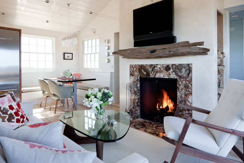 Small beach style living room next to the kitchen in a house with white walls, sofa and a rocking chair, brown granite fireplace, TV and a log of wood above the fireplace
