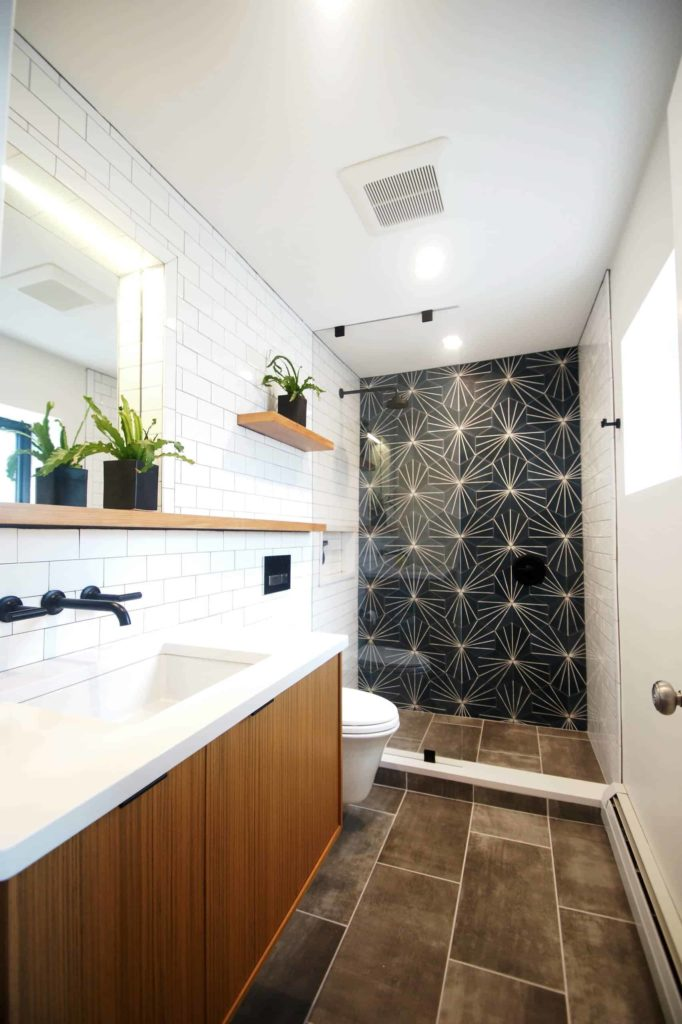 Brown tile floor, white tile walls, one wall is black pattern one