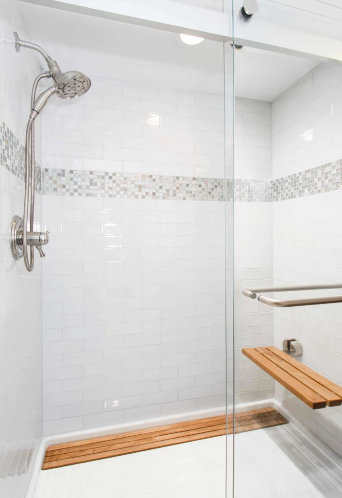 Transitional bathroom with white tile floor and walls, mosaic decoration