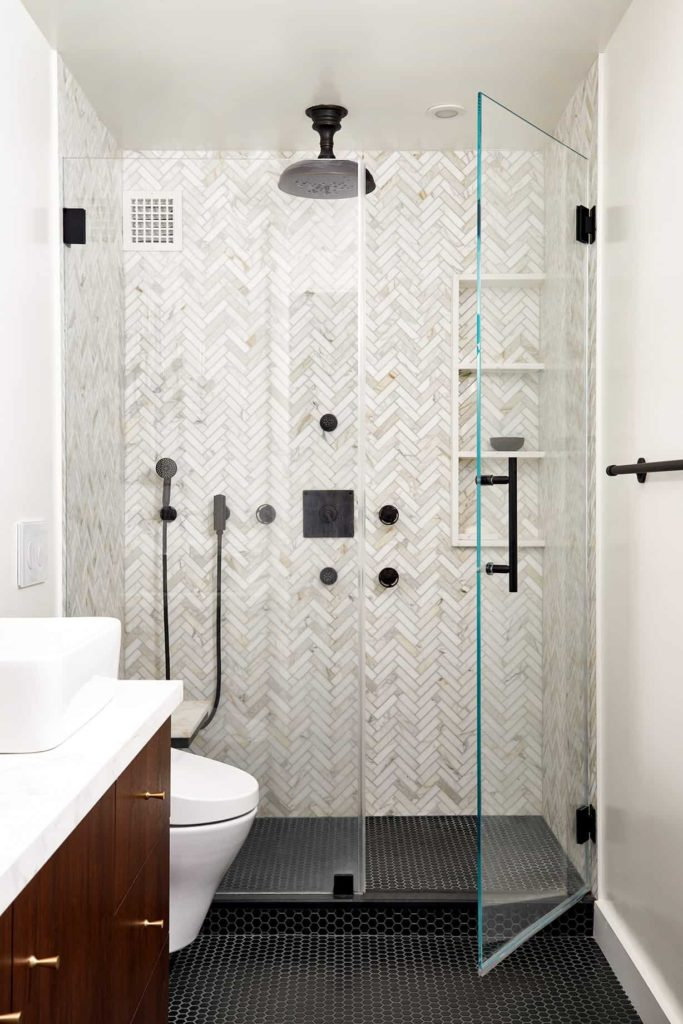 Alcove shower, black tile floor, white and grey mosaic walls