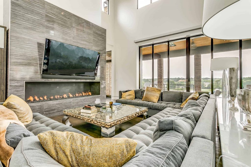 Spacious contemporary living room interior in a luxury apartment with cozy sofa, white walls, fireplace and a TV above the fireplace