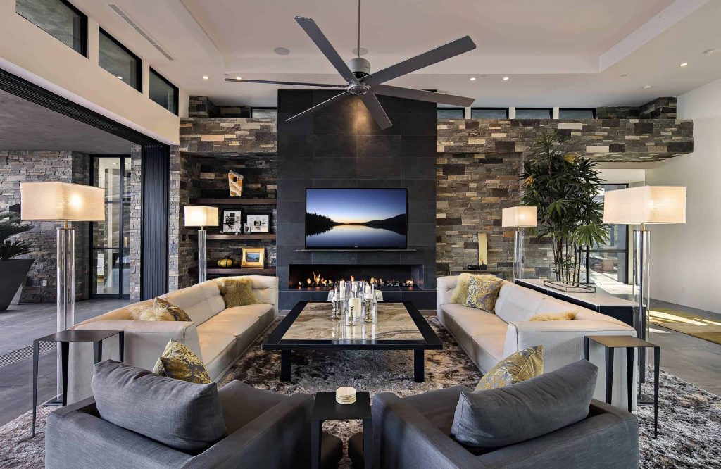 Spacious living room in a house with window wall, ceiling fan, dark grey tile floor, white sofas and grey chairs, wide fireplace in a black tile collumn and a TV above the fireplace