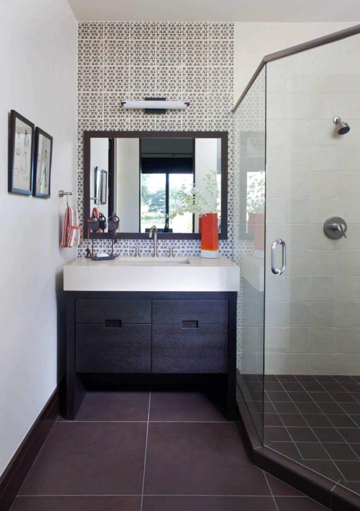 Corner shower, brown tile floor, white walls, dark wood cabinets