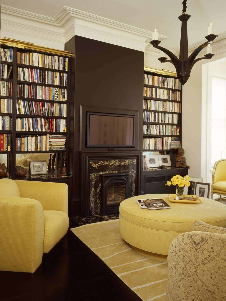Medium sized living room with dark brown floor and wall, white ceiling with a big brown chandelier, yellow comfy chairs, big bookcases, small fireplace and a TV above the fireplace