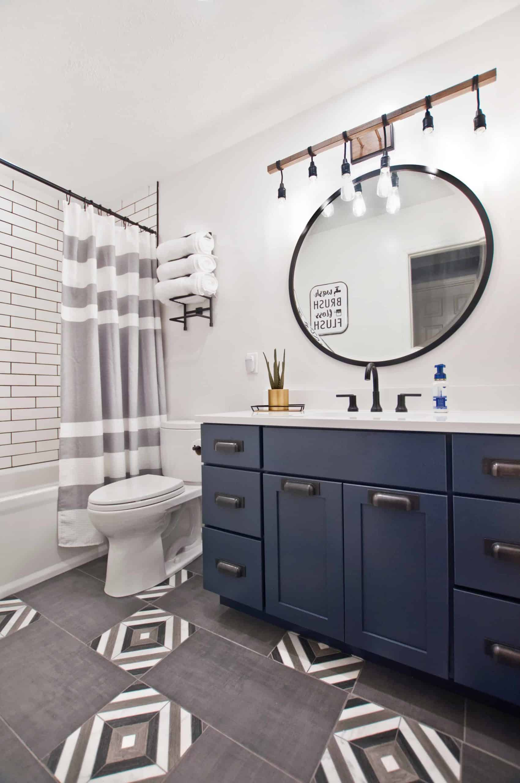 White walls, grey multi-colored tile floor, dark blue cabinets