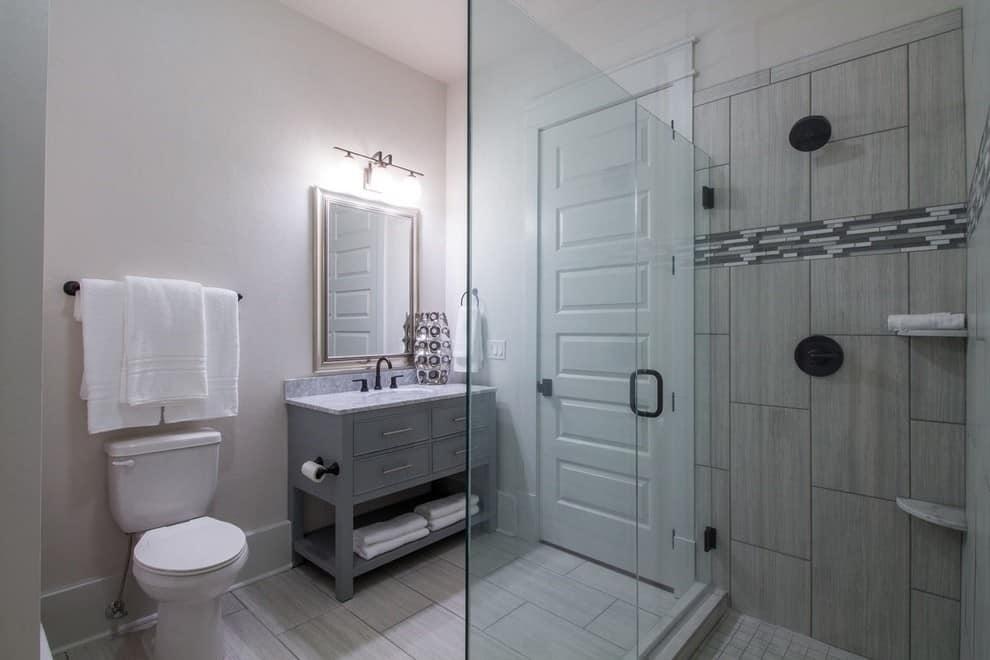Corner shower, white walls, grey cabinets, grey tile shower