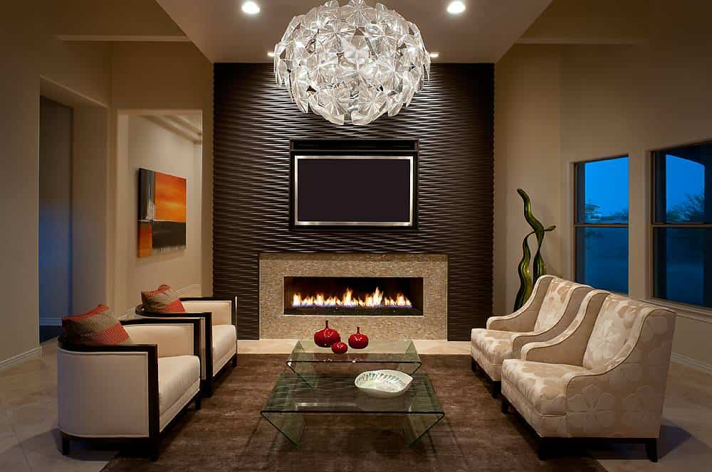 Small contemporary living room with beige walls, big glass chandelier, brown textured wall, beige armchairs, wide granite fireplace and a TV above the fireplace