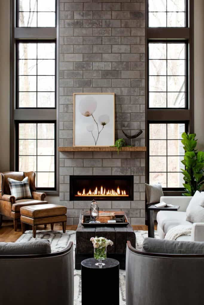 tiled fireplace ideas - graystone brick-like tile used here combined with the floor to ceiling windows is the perfect way to bring in natural light and make a statement