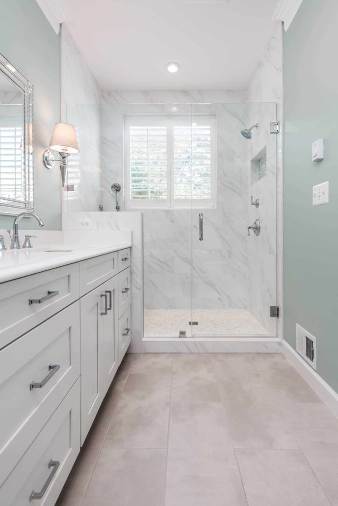 Alcove shower, white marble tiles, white cabinets