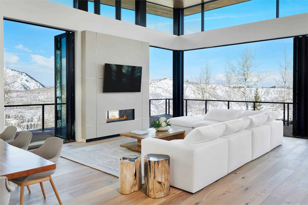 Spacious contemporary living room with a balcony and window walls, wooden floor, white walls and sofa, small fireplace and a TV above the fireplace