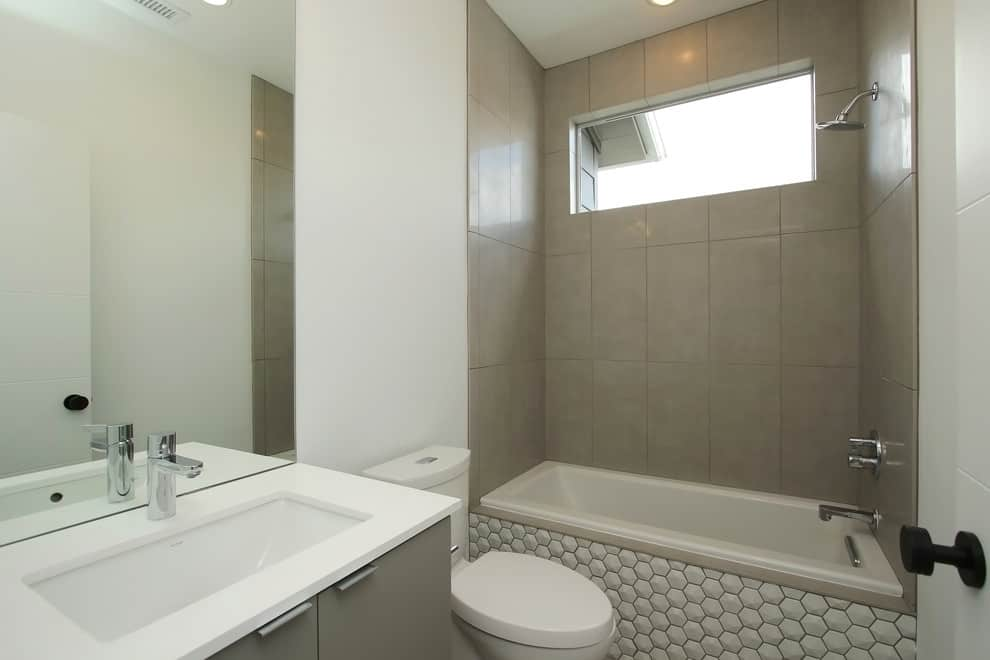 White honey comb tile bathtub, grey cabinets, grey tile walls