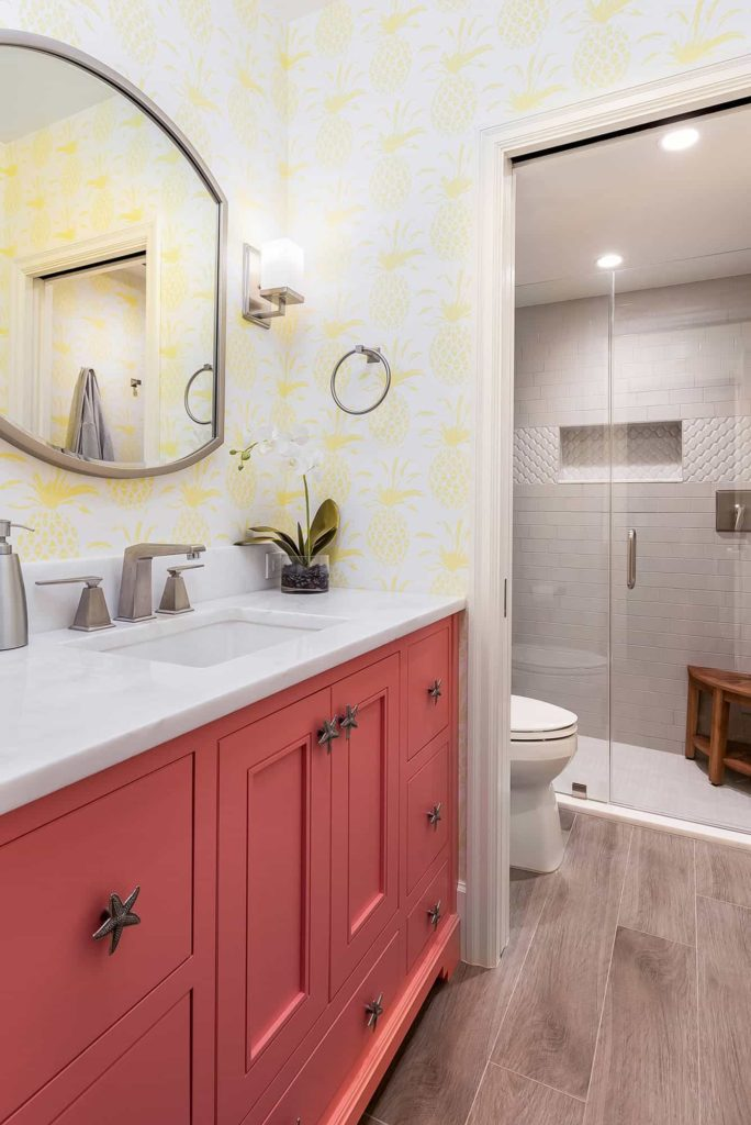 White tile shower, coral cabinets, yellow pineapple pattern wallpaper