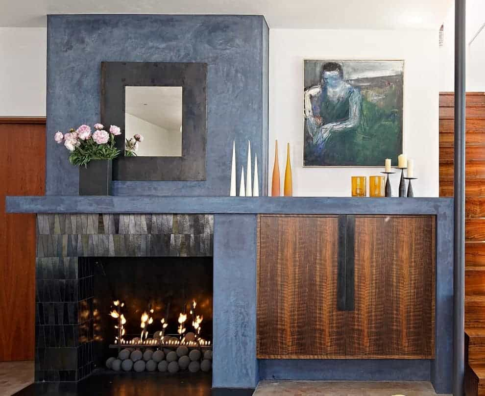 the shape and the dark metallic color of the tiles blend perfectly with the industrial look of the other half of the fireplace design