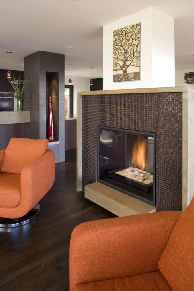 lighter colored solid surface hearth breaks up the space between the darker fireplace tile and flooring