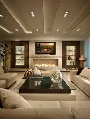 Spacious living room interior in beige colors with, sofa and chairs, glass-top coffee table and a wide marble fireplace