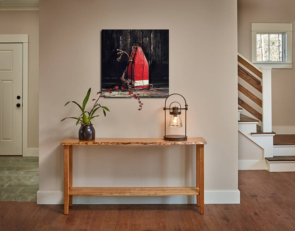 Sofa Table along a wall with a plant and lamp. Art hanging above it.