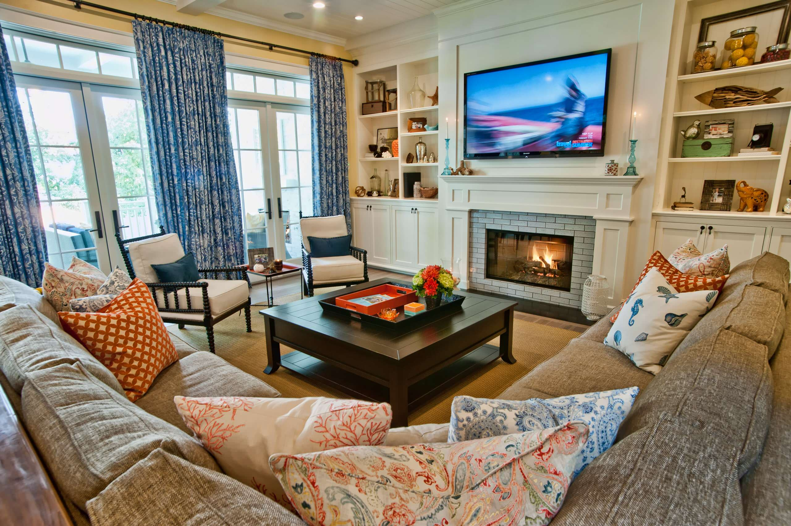 Example of a classic family room design in Los Angeles with yellow walls, a standard fireplace and a media wall, and a coffee table with a decorative tray